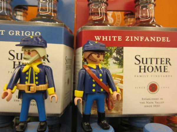 Two Civil War action figures in front of boxes of wine